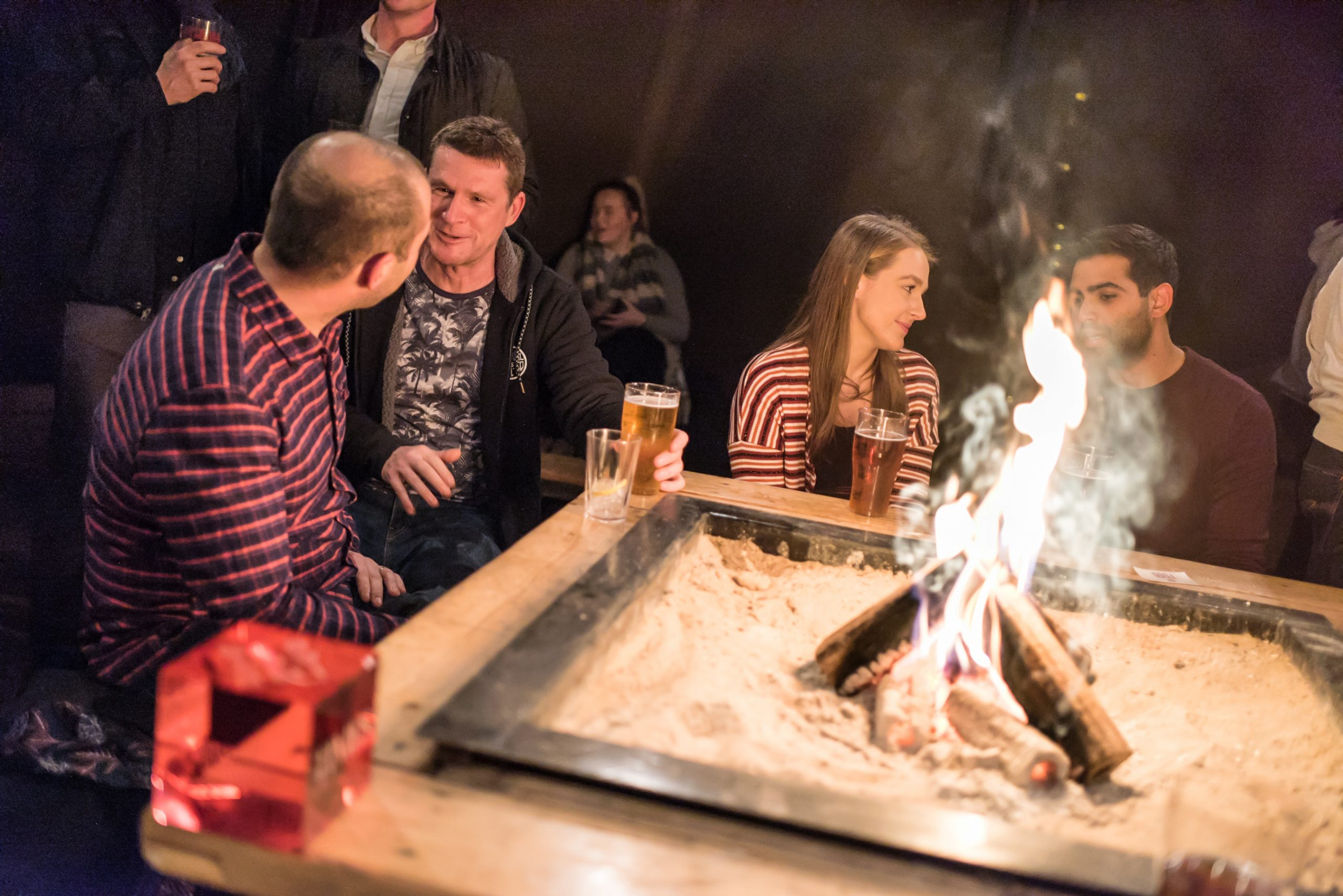 people enjoying a social gathering around a fire pit