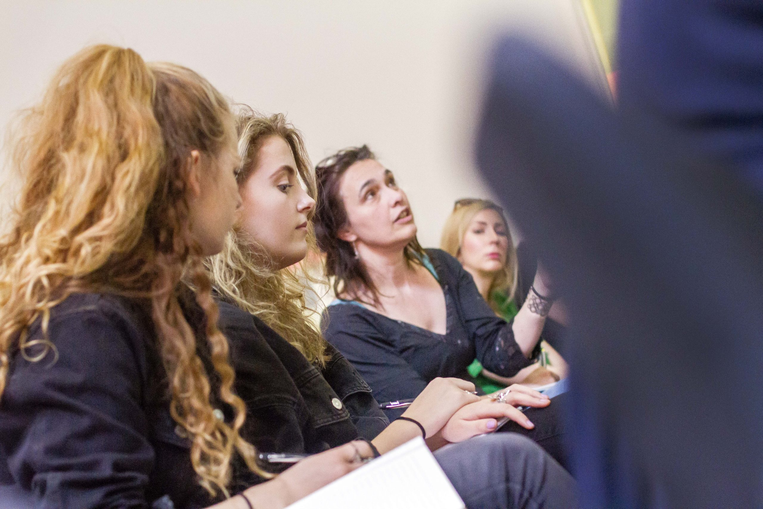 a group of women watching a panel discussion at the tipping point live 2019 conference
